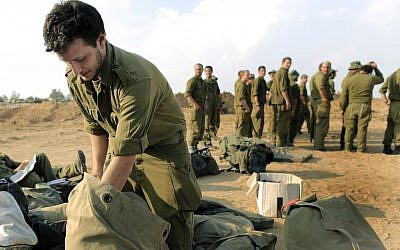 Illustrative: An Israeli reservist packs his gear after ending a deployment near Gaza during Operation Defensive Shield. (Tsafrir Abayov/ Flash90)