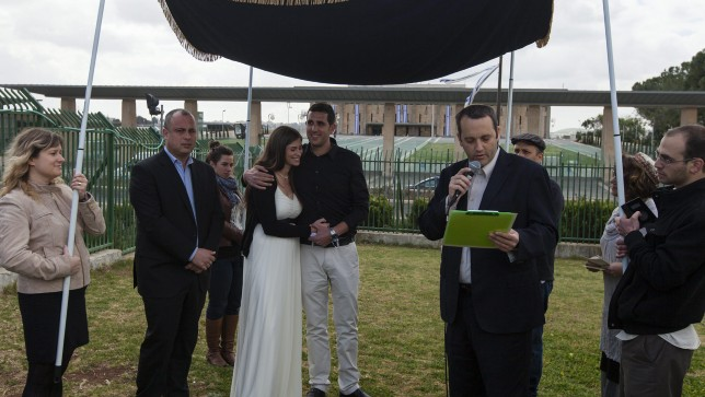 Rabbi Gilad Kariv, the head of the Reform movement in Israel, performs a Reform Jewish wedding ceremony in front of the Knesset, on March 18, 2013. To the left of the couple stands Labor party MK and secretary-general Hilik Bar. (photo credit: Flash90)