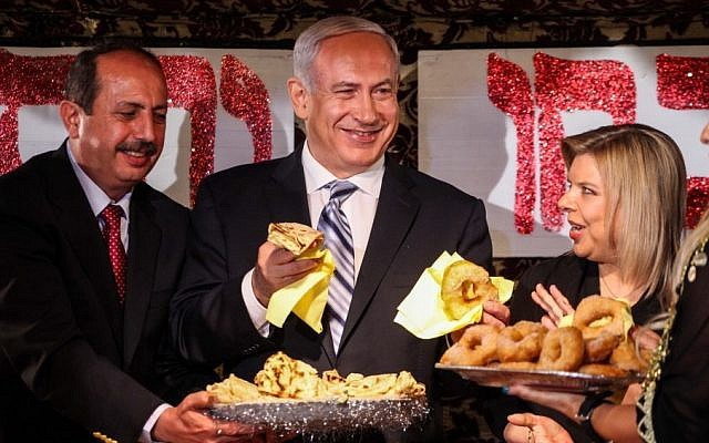 Prime Minister Benjamin Netanyau and his wife Sara enjoy 'mufletot' and traditional sweets at a colorful North African Mimouna celebration in Or Akiva, Monday. (photo credit: Avishag Shaar Yashuv/Flash90)