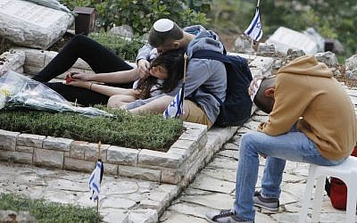 Israelis mourning at a gravesite on Mount Herzl in April. (photo credit:  Miriam Alster/Flash90)