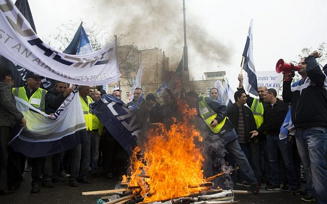 Israeli airline workers hold flags ans placards in front of tires burning during a demonstration outside the prime minister's office against the Open Skies agreement, on April 21, 2013 (photo credit: Yonatan Sindel/Flash90)