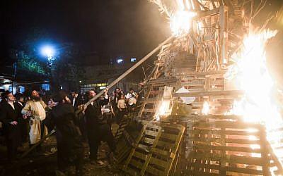 Ultra-Orthodox men set light to a massive bonfire during celebrations of the holiday of Lag B'Omer in Jerusalem on Saturday, April 27, 2013. (photo credit: Yonatan Sindel/Flash90)