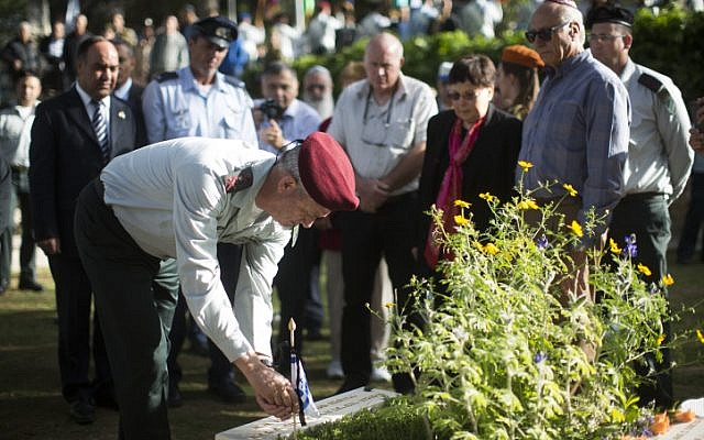 IDF Chief of Staff Benny Gantz putting an Israeli flag on the grave of a soldier at Mount Herzl,  April 10, 2013. (photo credit: Yonatan Sindel/Flash90)
