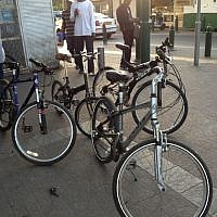 African refugees and their bicycles on a Tel Aviv street (photo credit: Jessica Steinberg)