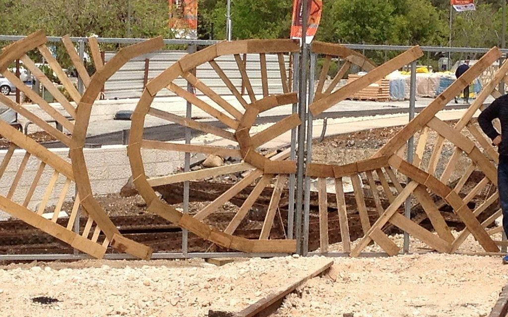 A local urban artist is creating a hand-constructed fence at the Station, made from recycled pieces of wood. (photo credit: Jessica Steinberg/Times of Israel)
