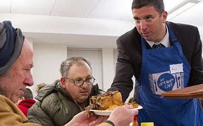 Deputy Education Minister MK Avi Wortzman (Jewish Home) helps serve dinner to guests at the Chicago Federation's kosher, restaurant-style hunger program for the city's impoverished residents. (photo credit: Steve Donisch)