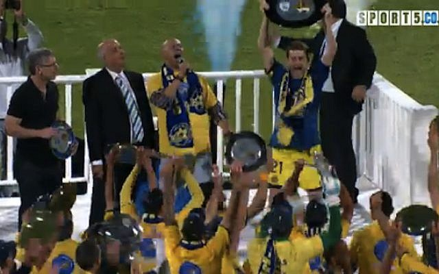 Maccabi Tel Aviv Team captain Shiran Yeini hoists the championship trophy before 33,000 delighted fans at Ramat Gan Stadium Monday, April 22 (image capture: Channel 5)