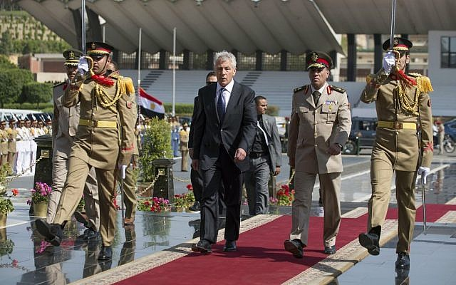 US Secretary of Defense Chuck Hagel, center, arrives with an Egyptian army official to lay a wreath at the Tomb of the Unknown Soldier and the tomb of late president Anwar al-Sadat in Cairo on Wednesday, April 24, 2013 (photo credit: AP/Jim Watson, Pool)