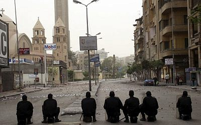 Illustrative photo of Egyptian riot police watching over a Coptic cathedral in the early hours of Monday, April 8, 2013, in Cairo, Egypt. (photo credit: AP)