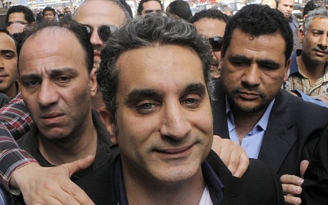 A bodyguard secures popular Egyptian television satirist Bassem Youssef, who has come to be known as Egypt's Jon Stewart, as he enters Egypt's state prosecutors office to face separate accusations of insulting Islam and the country's Islamist leader in Cairo, Egypt, on March 31, 2013 (photo credit: AP Photo/Amr Nabil, File)