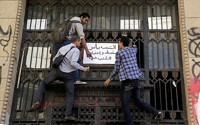 "Egyptian protesters hang an Arabic banner reading, ""people demand an arrest warrant to the prosecutor general"" during a protest in front of the prosecutor general's office in Cairo, Egypt, Friday, March 29, 2013. (Photo credit: AP/Amr Nabil)"