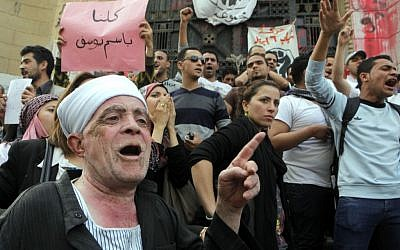 Egyptian activists shout anti-Muslim brotherhood slogans in front of Egypt's state prosecutors office in support of popular Egyptian television satirist Bassem Youssef, in Cairo, Egypt, Sunday, March 31, 2013.  (Photo credit: AP/Amr Nabil)