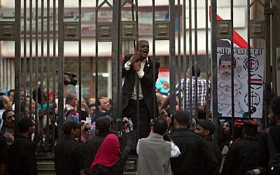 An Egyptian man chants slogans as another holds a cartoon of Egypt's president, Mohammed Morsi during a protest in front of the judges club in downtown Cairo, Egypt, Wednesday, April 24, 2013. (photo credit: AP/Khalil Hamra)