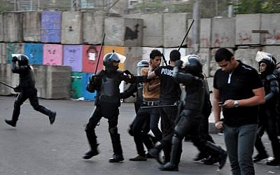 Egyptian riot police detain a protester during clashes outside the presidential palace in Cairo, April 2013 (photo credit: AP/Hussein Tallal)