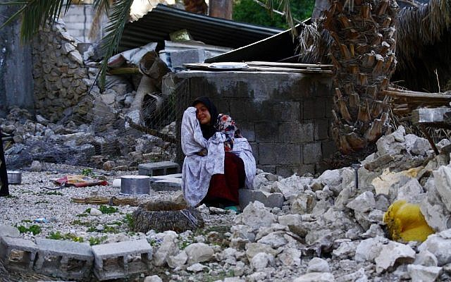An Iranian woman reacts as she sits among the rubble of buildings after an earthquake struck southern Iran, in Shonbeh, Iran in April. (photo credit: AP/Fars News Agency, Mohammad Fatemi)