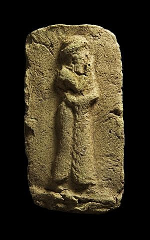 A clay plaque which shows a worshiper approaching a sacred place, wearing a long robe with fringe down the front opening. It was found during the excavation Tell Khaiber, Iraq. (photo credit: AP Photo/Stuart Campbell)