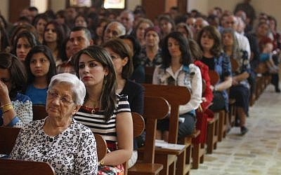 Iraqi Christians pray during Easter mass at Mar Youssif Chaldean Church in Baghdad on Sunday. The Chaldean Church is an Eastern Rite church affiliated with the Roman Catholic Church. (photo credit: AP Photo/ Karim Kadim)