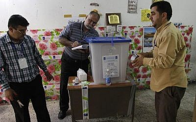 Iraqi election officials check the seals on a ballot box before the country's provincial elections at a polling center in Baghdad, Iraq, Saturday, April 20, 2013.  (AP Photo/ Khalid Mohammed)