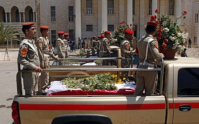 Security forces escort the coffins of five slain soldiers at the headquarters of the Iraqi Ministry of Defense in Baghdad, Iraq, Sunday, April 28, 2012. Gunmen killed 10 people in Iraq, including five soldiers near the main Sunni protest camp west of Baghdad on Saturday, the latest in a wave of violence that has raised fears the country faces a new round of sectarian bloodshed. (Photo credit: AP/Hadi Mizban)