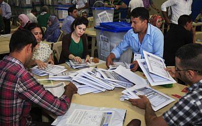 Electoral workers tally ballots at a counting center in Baghdad, Iraq, Sunday, April 21, 2013. (photo credit: AP/Karim Kadim)