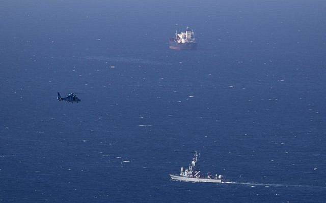 An Israeli military naval ship and an Israeli air force helicopter operate off the coast of Haifa on Thursday searching for debris from a downed drone. (photo credit:AP/Ariel Schalit)
