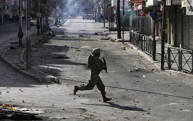 An Israeli soldier in Hebron during clashes with Palestinians in April. (photo credit: AP/Nasser Shiyoukhi)