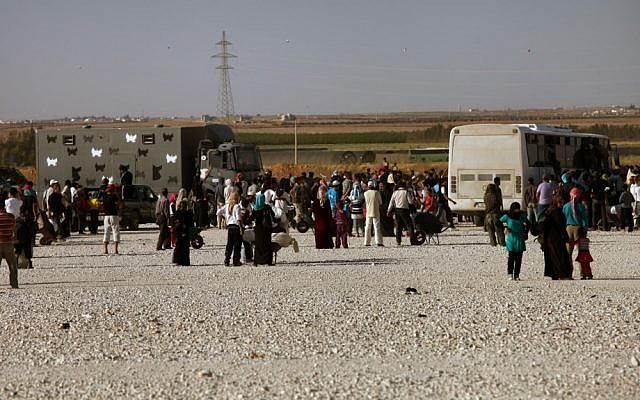 Syrian refugees carry their belongings as they wait to board a military bus from the Zaatari refugee camp, near the Syrian border en route to the border to cross into Syria again in April 2013. (photo credit: Mohammad Hannon/AP)