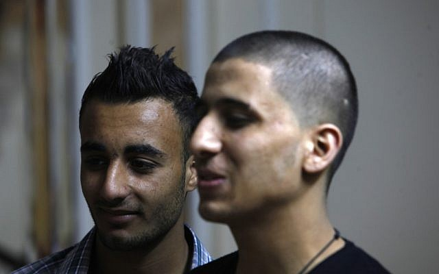 Ayman al-Sayed, 19, right, with his hair cut, stands with his friend Mohammed Hanouna, 18, left, in Gaza City, Sunday, April 7, 2013. Al-Sayed used to have shoulder-length hair but says he was grabbed by Hamas police in a sweep along with other young men with long or gel-styled spiky hair last week, and that police shaved everyone's head. Hanouna still wears the hair-style that can now get young men in trouble in Gaza, during the Islamic militants latest attempt to impose their hardline version of Islam on Gaza. (photo credit: AP/Adel Hana)