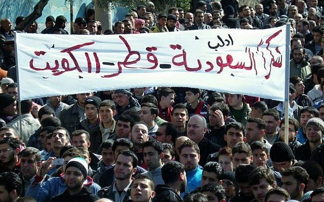 """Anti-Syrian regime protesters hold up a banner in Arabic reading: """"Thank you Saudi Arabia, Qatar and Kuwait,"""" during a demonstration, in Idlib province, northern Syria, in March 2012. (photo credit: AP/Local Coordination Committees in Syria)"""