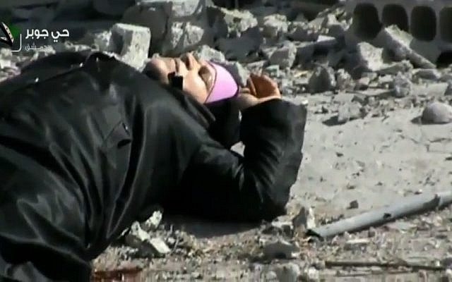An injured Syrian woman lying in a street before her rescue by rebels, Wednesday, April 10, 2013. (photo credit:AP/Shaam News Network via AP video)