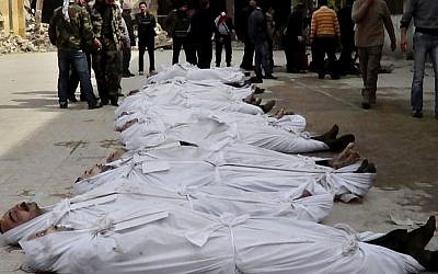 This file citizen journalism image taken on, Sunday, March. 10, 2013 and provided by Aleppo Media Center AMC which has been authenticated based on its contents and other AP reporting, shows Syrians standing next to dead bodies that have been pulled from the river near Aleppo's Bustan al-Qasr neighborhood, Syria (photo credit: AP/AMC)