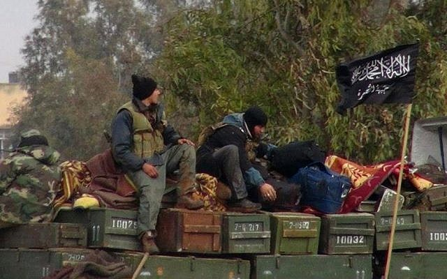 Rebels from al-Qaeda affiliated Jabhat al-Nusra, as they sit on a truck full of ammunition, at Taftanaz air base in northern Syria. (photo credit: AP/Edlib News Network ENN, File)