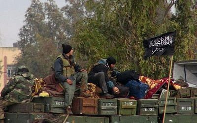 This Friday, Jan. 11, 2013 file citizen journalism image shows rebels from al-Qaida affiliated Jabhat al-Nusra, as they sit on a truck full of ammunition, at Taftanaz air base, that was captured by the rebels, in Idlib province, northern Syria (photo credit: AP/ENN)