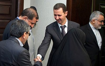 Syrian President Bashar Assad (center), shakes hands with a member of Iran's parliamentary committee on national interest and foreign policy, in Damascus, Syria, April 22, 2013. (photo credit: AP/SANA)