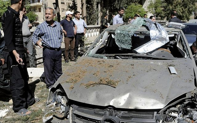 This photo released by the Syrian official news agency SANA, shows Syrians inspecting a damaged car at the scene of a car bomb exploded in the capital's western neighborhood of Mazzeh, in Damascus, Syria, Monday, April. 29, 2013 (photo credit: AP/SANA)