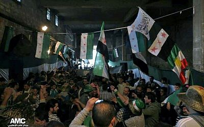 Anti-Syrian regime protesters holding Syrian revolution flags, during a rally marking the anniversary of the 1946 withdrawal of French troops from Syria, which marked the end of France's mandate of the Arab country, in the old quarter of the northern city of Aleppo, Syria, on Wednesday, April 17, 2013. (photo credit: AP Photo/Aleppo Media Center AMC)