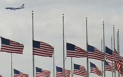 A jetliner flies over flags flying at half-staff at the Washington Monument in Washington, Tuesday, April 16, 2013, after President Obama ordered flags to be lowered on federal building to honor the loss of life from the explosions at the Boston Marathon. (photo credit: AP/J. David Ake)