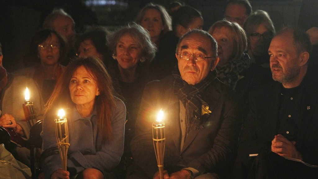 Participants listen to a short concert as Julian Rachlin, the first violinist with the Israel Philharmonic Orchestra, plays a Bach sarabande in front of the monument to the fighters of the Warsaw ghetto uprising in Warsaw, Poland, on Thursday (photo credit: AP/Czarek Sokolowski)