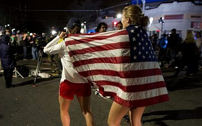 Taylor Richard, center, of Belmont, Mass., and Alyssa Kohler, 17, of Cambridge, Mass., wrap themselves in the American Flag in Watertown, Mass., Friday, April 19, 2013 after the arrest of the second bombing suspect, Dzhokbar Tsarnaev. (AP Photo/Craig Ruttle)