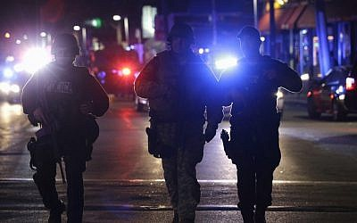 Officers wearing tactical gear arrive in Watertown, near Boston, on Friday (photo credit: AP/Julio Cortez)
