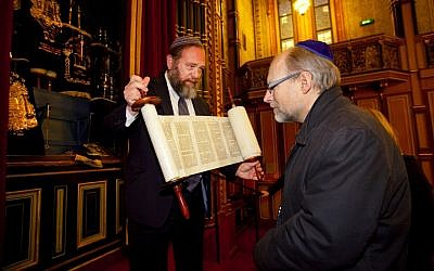 Rabbi David Lazar, left, showing a Torah scroll to Swedish government minister Stefan Attefall at the Great Synagogue of Stockholm, November 2011. (photo credit: Regeringskansliet, The government of Sweden/JTA)