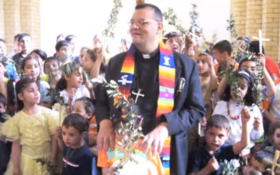 Canon Andrew White at St. George's Church, Baghdad, with children from his congregation (screenshot: YouTube)
