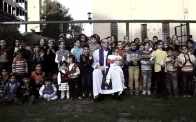 Canon White with children outside his Baghdad church before prayers in February (YouTube screenshot)