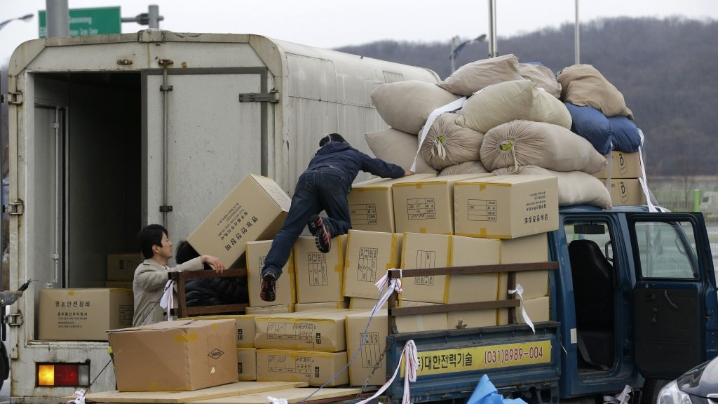 A South Korean man, center, unloads boxes transported from North Korea's Kaesong upon arrival at the customs, immigration and quarantine office near the border village of Panmunjom, which has separated the two Koreas since the Korean War, in Paju, north of Seoul, South Korea, on Tuesday. (photo credit: AP Photo/Lee Jin-man)