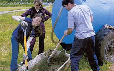US college students preparing some cement as part of a restoration project for a Belarus Jewish cemetery, 2012. (photo credit: Restoration of Eastern European Jewish Cemeteries Foundation/JTA)