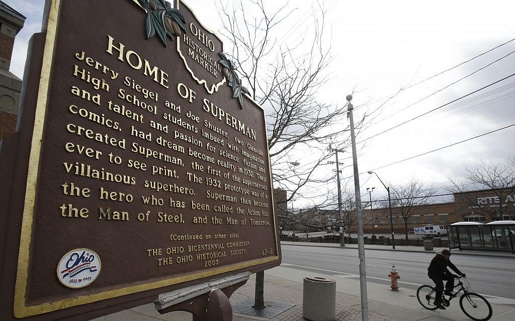 A man riding his bicycle past the Home of Superman plaque in Cleveland. (photo credit: AP Photo/Tony Dejak)