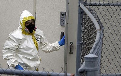 A Prince George's County, Md. firefighter dressed in a protective suit walks into a government mail screening facility in Hyattsville, Md., on Wednesday, (photo credit: AP/Alex Brandon)
