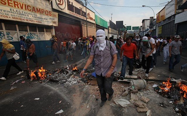Opposition supporters and students cross a barricade during clashes with riot police in Caracas, Venezuela, on Monday, April 15, 2013. (photo credit: AP Photo/Fernando Llano)