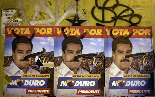 Defaced campaign signs of ruling party presidential candidate Nicolas Maduro cover a wall in Caracas, Venezuela, Friday, April 12 (photo credit: AP/Ariana Cubillos)