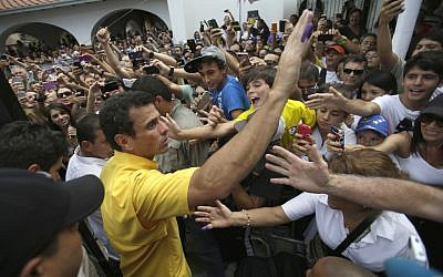 Opposition presidential candidate Henrique Capriles greets supporters after voting in the presidential election outside a polling station in Caracas, Venezuela, Sunday, April 14, 2013. Capriles is running for president against Nicolas Maduro, the hand picked successor of late President Hugo Chavez. (photo credit: AP/Fernando Llano)